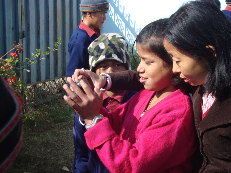 Children learning to operate digital camera